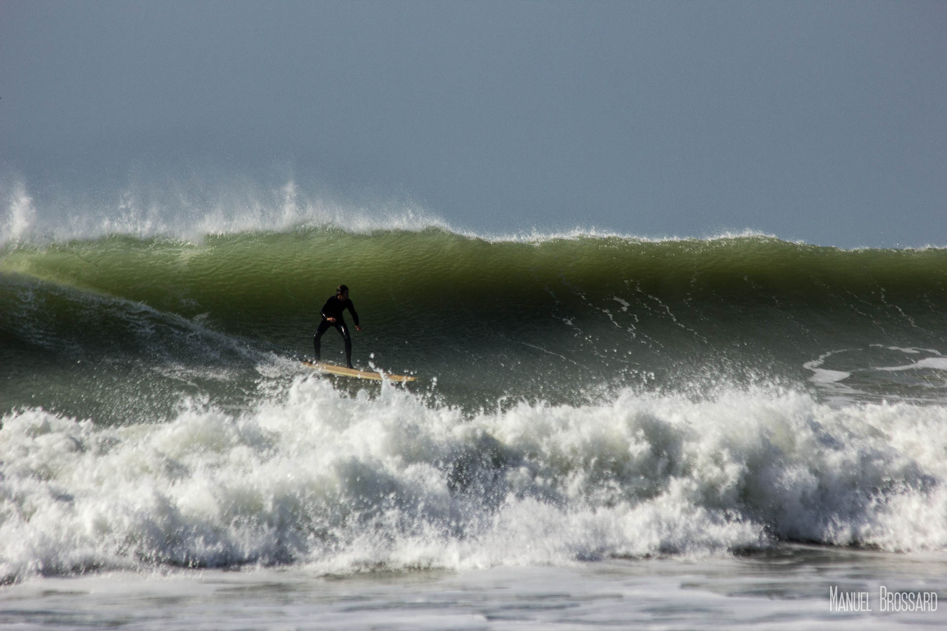 Un surfeur ride une vague glassy